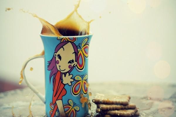 Una alegre taza con gafé junto a unas galletas