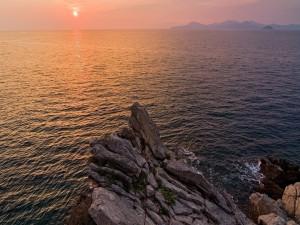 Postal: Los rayos del sol se reflejan sobre las aguas del océano