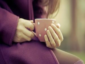 Las manos de una mujer sosteniendo una taza