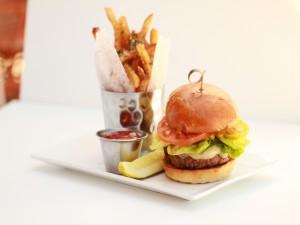 Una hamburguesa acompañada de salsa y patatas fritas