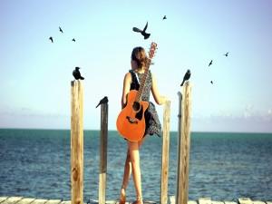 Mujer con su guitarra contemplando el mar