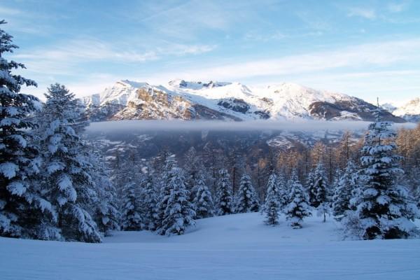 El sol iluminando las montañas nevadas