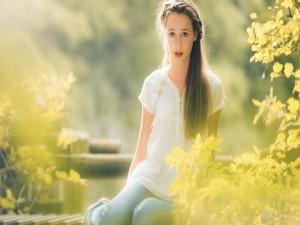 Muchacha con un bonito peinado sentada entre las plantas