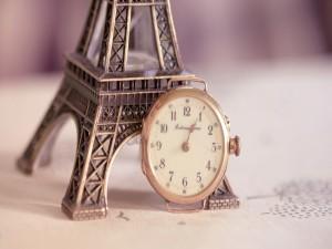 Reloj sin correa junto a una Torre Eiffel en miniatura