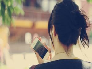 Postal: Mujer con un móvil en la mano