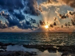 Postal: Brillante sol visto desde la orilla del mar