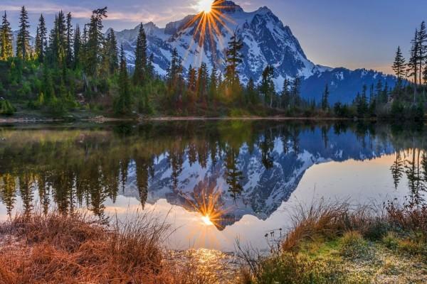 El sol y la montaña reflejados en el lago