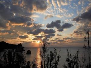 Postal: El sol entre las nubes al amanecer