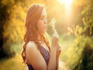 Chica contemplando unas flores silvestres