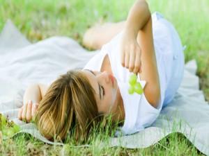 Postal: Mujer sobre la hierba con un vestido blanco