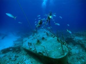 Buzos y peces ciernen sobre los restos de un barco en las Islas Caimán
