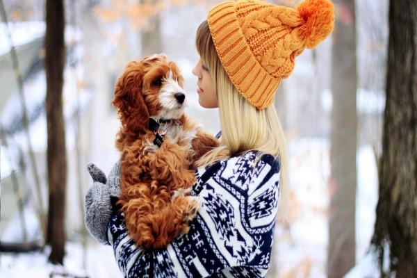 Joven con un lindo perro en sus brazos