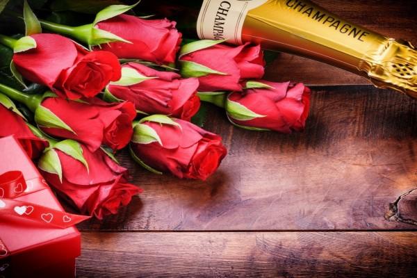 Rosas rojas, regalo y una botella de champán para festejar San Valentín