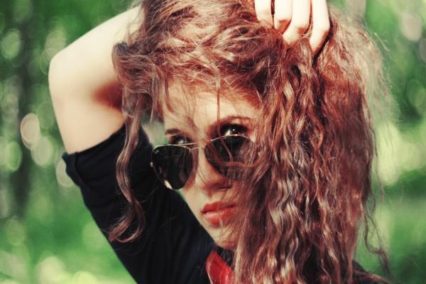 Chica con el pelo rizado y gafas de sol