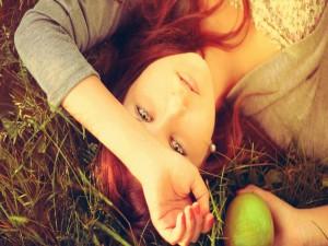 Una chica tumbada con una manzana en su mano