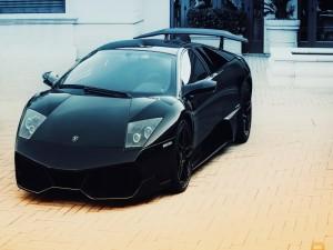 Postal: Lamborghini negro junto a una casa