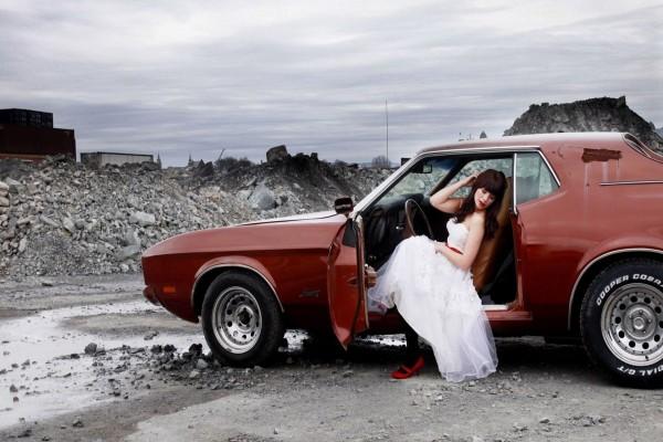 Mujer con vestido de novia sentada en un coche