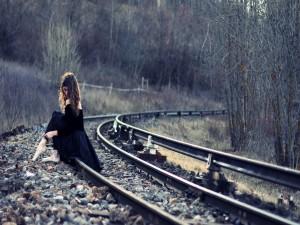 Postal: Mujer con zapatillas de ballet sentada en la vía de tren