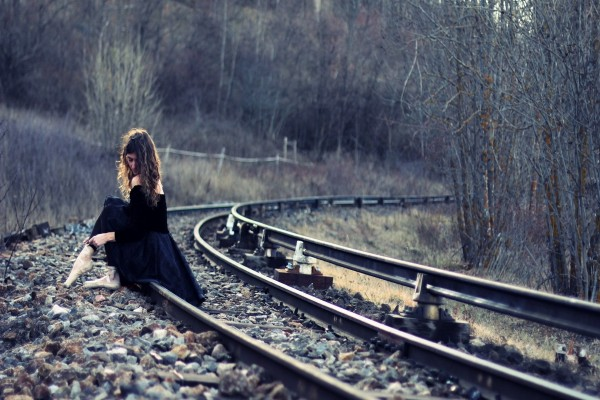 Mujer con zapatillas de ballet sentada en la vía de tren