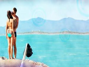 Postal: Pareja besándose junto al mar