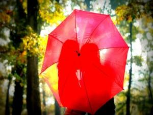 Pareja de enamorados detrás de una sombrilla
