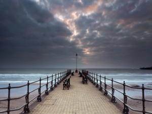 Nubes sobre el mar y el muelle