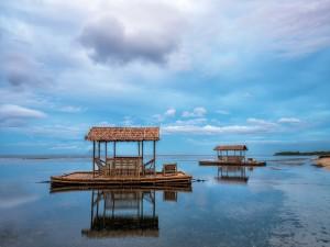 Postal: Barquetas flotantes de madera sobre el mar