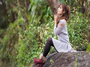 Bella mujer sentada en una piedra