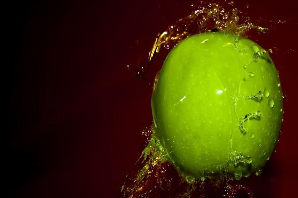 Salpicaduras de agua en una manzana verde