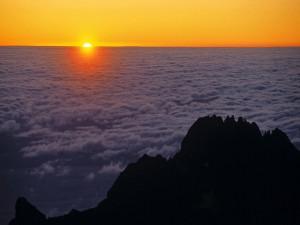 Postal: El sol asomando entre un mar de nubes