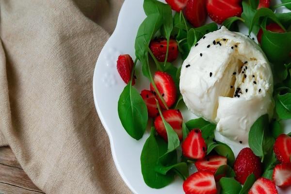 Helado de queso acompañado de fresas y hojas verdes