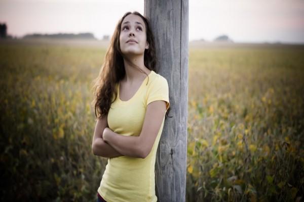 Chica pensando apoyada en un tronco
