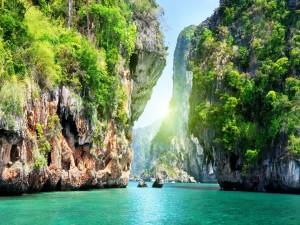 El sol asomando entre las enormes rocas del mar