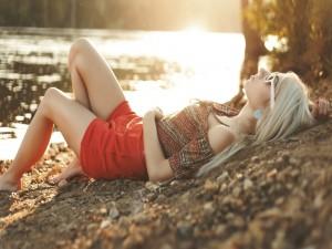 Chica tumbada junto a la orilla de un río
