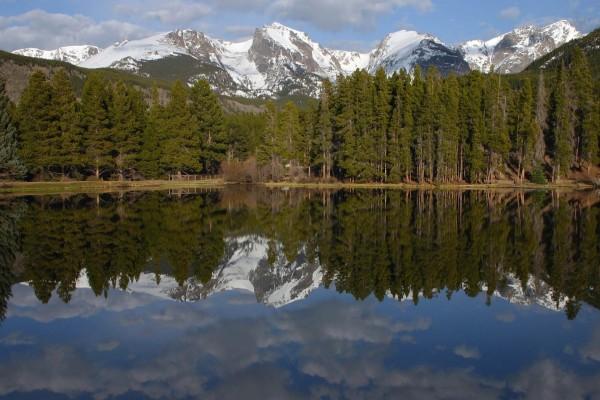 Montañas nevadas tras el lago y el bosque