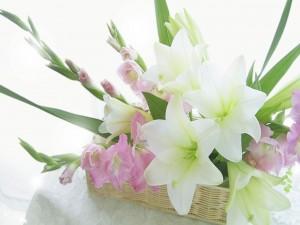 Una cesta con gladiolos y lirios