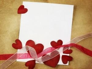 Corazones, cintas y papel para elaborar una tarjeta en San Valentín