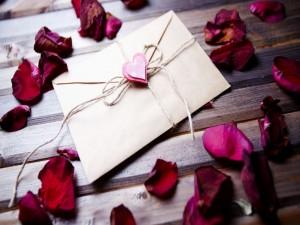 Una carta de amor junto a pétalos de rosas para San Valentín