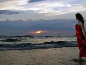 Postal: Dama de rojo admirando el mar