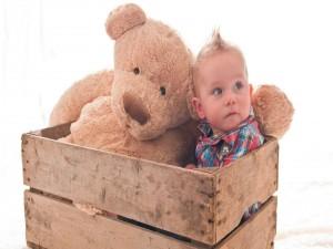 Postal: Bebé en una caja junto a un gran oso de peluche