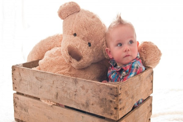 Bebé en una caja junto a un gran oso de peluche