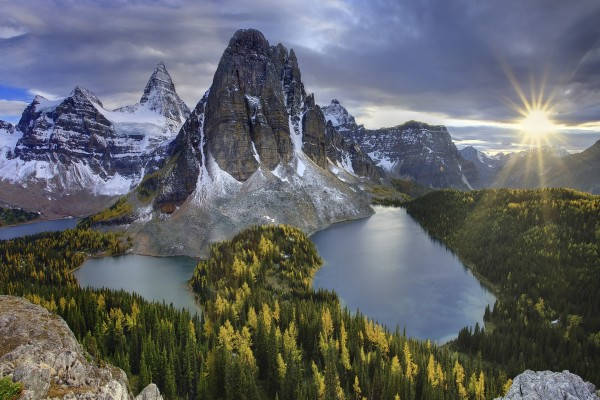 Brillante sol del amanecer iluminando montañas y lagos