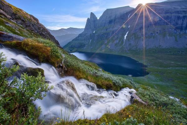 Primeros rayos de sol tras la montaña iluminan el bello paisaje