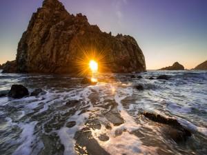 El sol brillando en el hueco de una roca marina