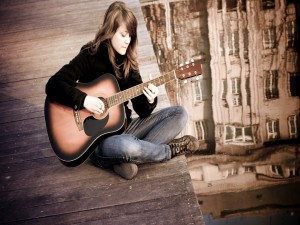 Mujer tocando la guitarra sentada en el muelle
