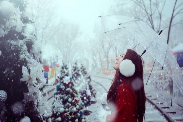 Chica con un paraguas bajo la nieve