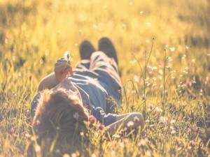 Postal: Niño tumbado en el campo soplando a un diente de león