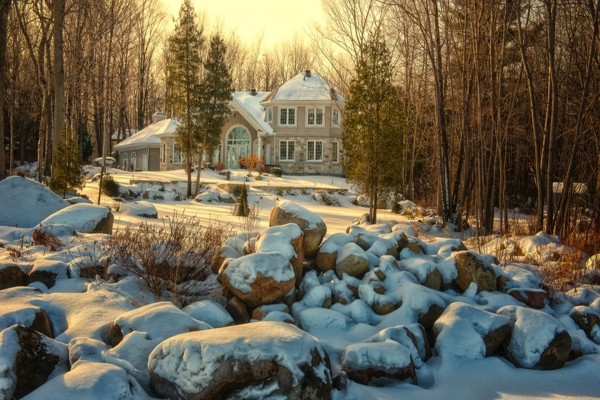 Rocas cubiertas de nieve en el jardín de una gran casa