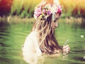 Joven con una corona de flores en el agua