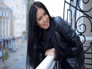 Postal: Chica sonriendo en un balcón